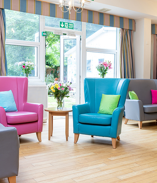 Bright sitting area with turqoise and pink arm chairs in front of a large window area